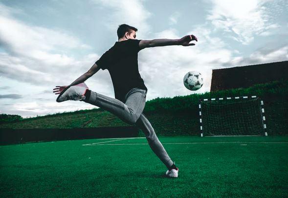 homme en survetement frappe dans un ballon de foot