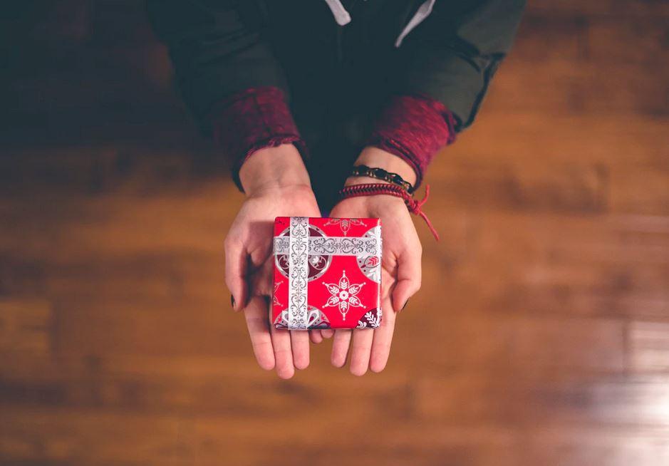 femme qui tient un petit cadeau dans ses mains